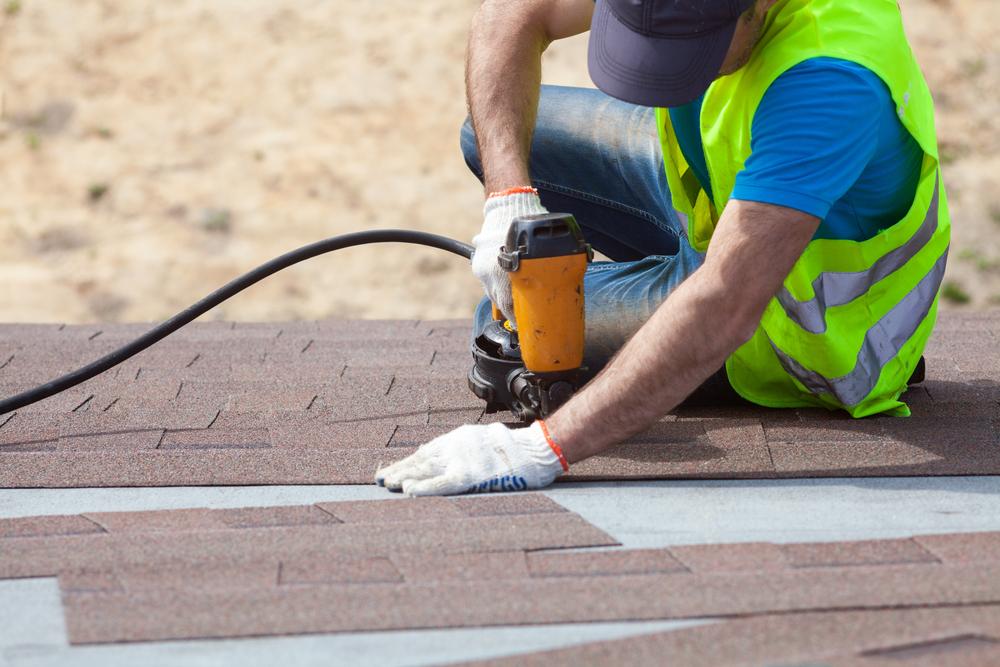 Roofer builder worker with nailgun installing Asphalt Shingles