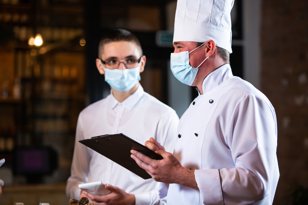 the chef conducts a briefing of employees in the restaurant
