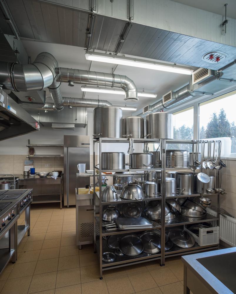 Restaurant kitchen equipment. Stainless steel pots on the shelves.