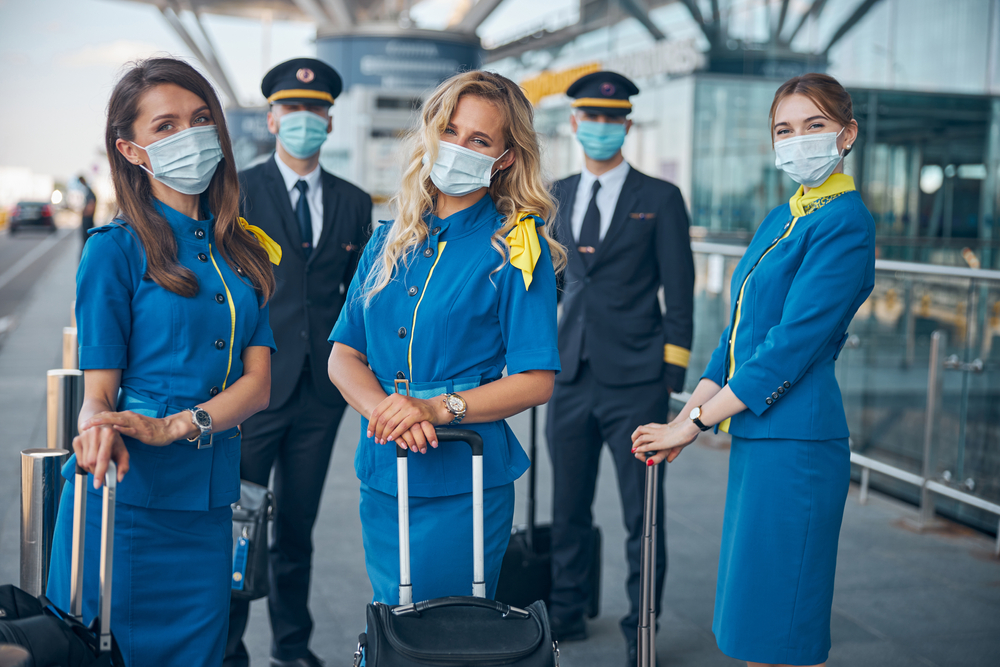 Charming flight attendants and pilots in protective face masks waiting for flight at airport