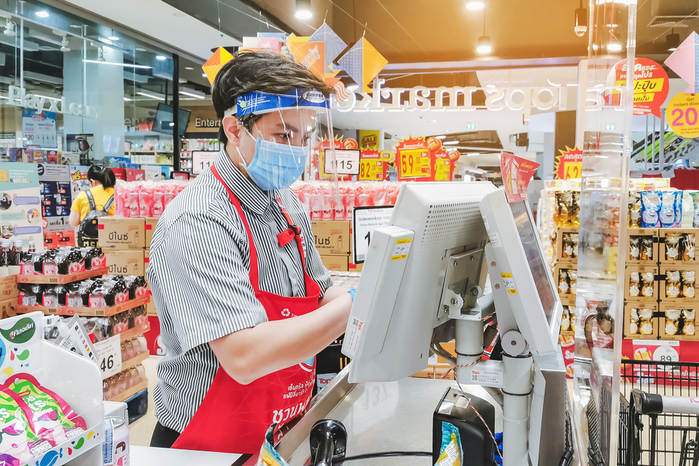 Unidentified Cashier or supermarket staff and customers in medical protective mask