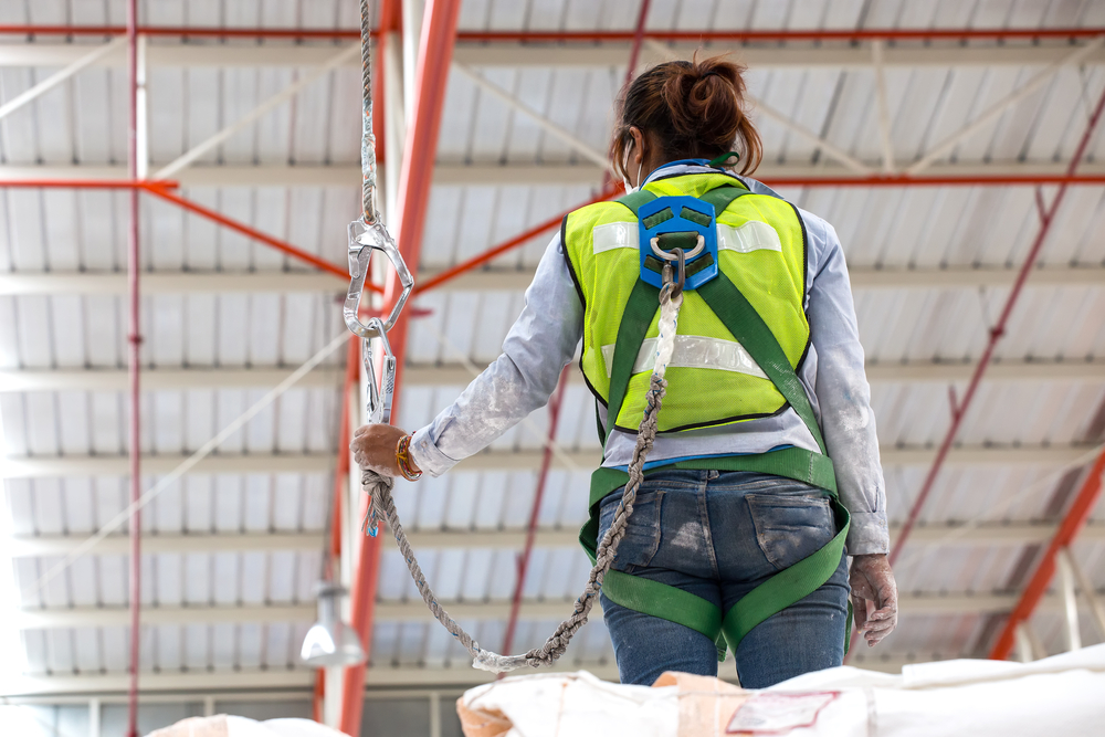 a girl with a safety harness on a jobsite