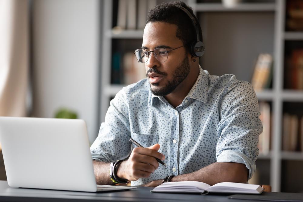 Focused young african businessman wear headphones study online