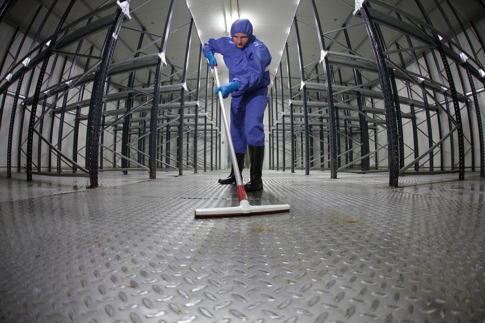 worker in protective overalls cleaning floor in empty storehouse