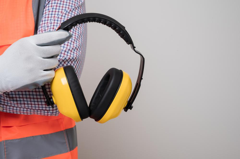 Close up male hand civil engineer holding earmuff