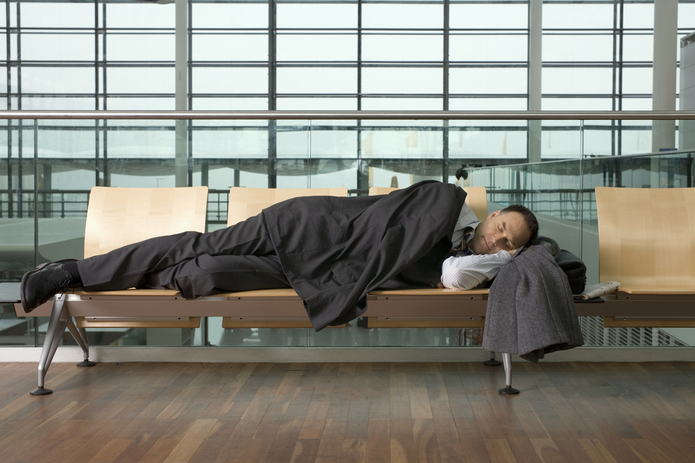 A businessman asleep in airport lounge.