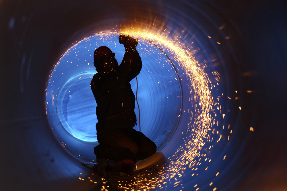 A worker works inside a pipe on a pipeline construction welding