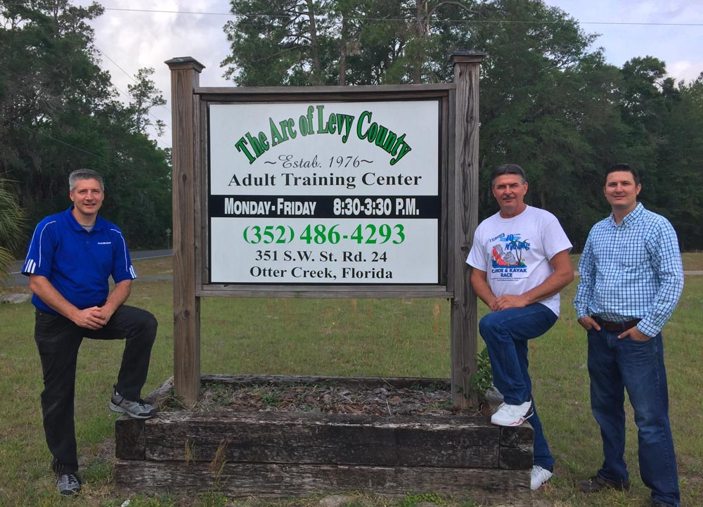 LARC directors standing in front of sign for The Arc of Levy County.