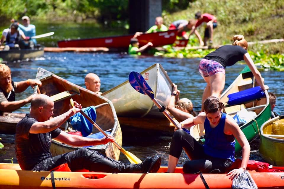 Several groups of canoe race participants get piled up near the finish line.