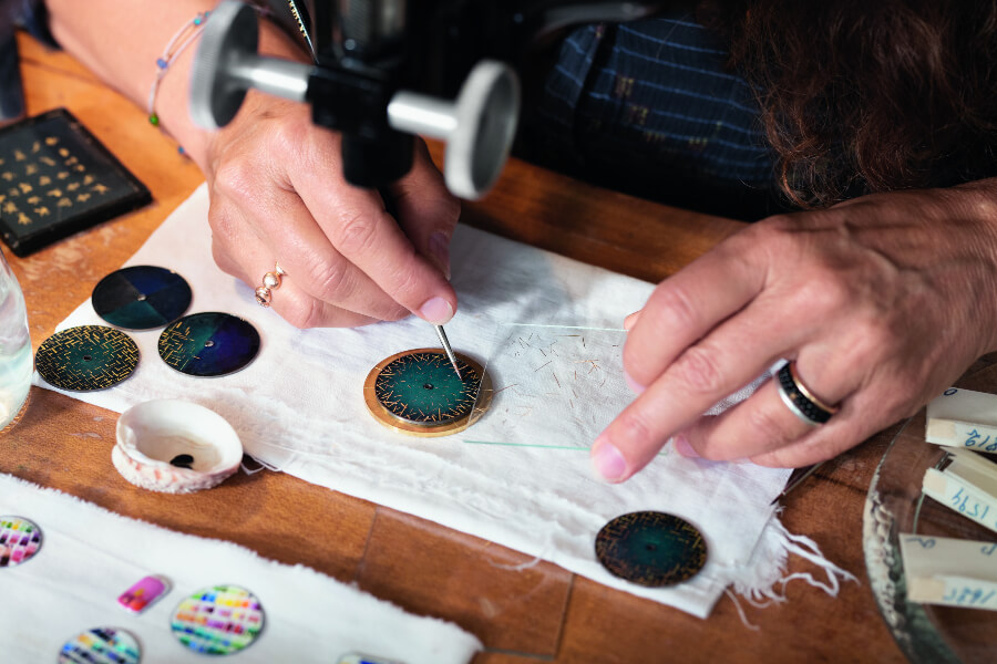 Anita Porchet is carefully positionning by hand each unique gold spangle on the blue enamelled dial