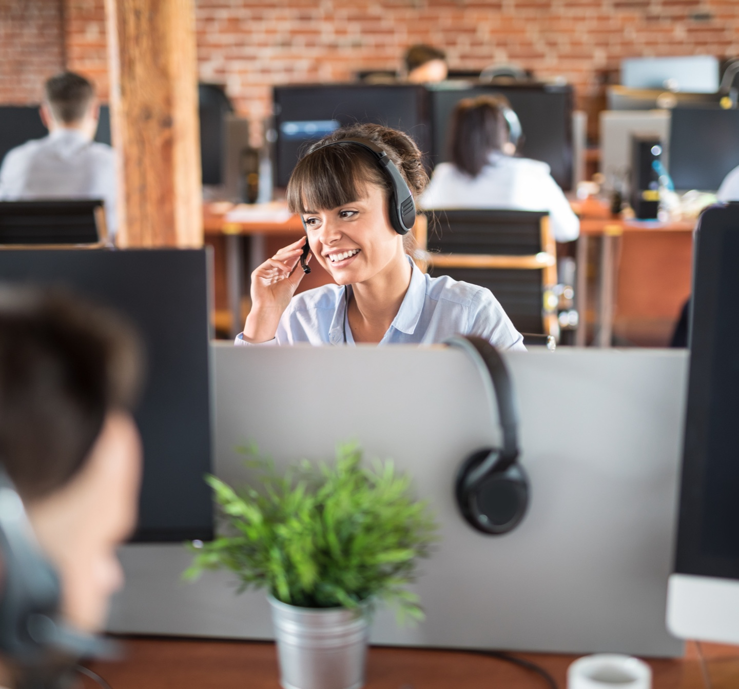 Customer service representative with headset on computer