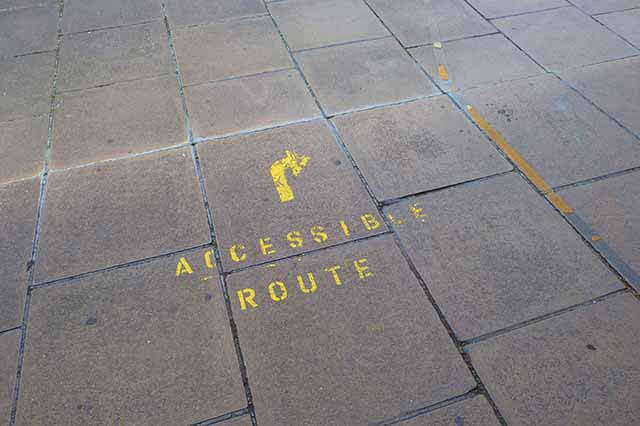 Concrete painted with an arrow and the words Accessible Route