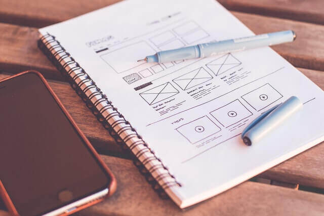 A notebook with website layouts sketched on its pages.