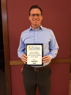 Photo of Adam Lombardo holding a thank-you plaque from Voices for Children.