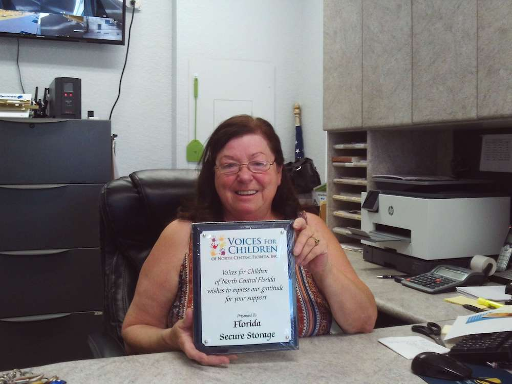 Photo of Kathy Rogers of Florida Secure Storage holding a thank-you plaque.