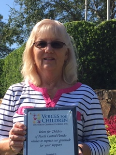 Photo of Paula Pombier holding a plaque from Voices for Chidlren