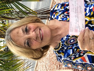 Sue Carpenter of Voices for Children holding a check from Orphan's Rock to Voices for Children of North Central Florida.