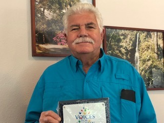 Wilbur Vanwyck holding up a plaque from Voices for Children of North Central Florida