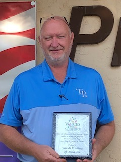 Tom Ready of Wood's Printing holding a recognition plaque for our sponsors