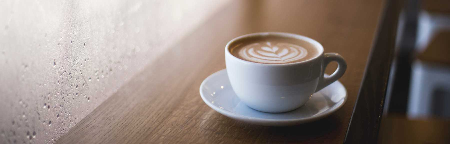 Picture of coffee in a cup by a window
