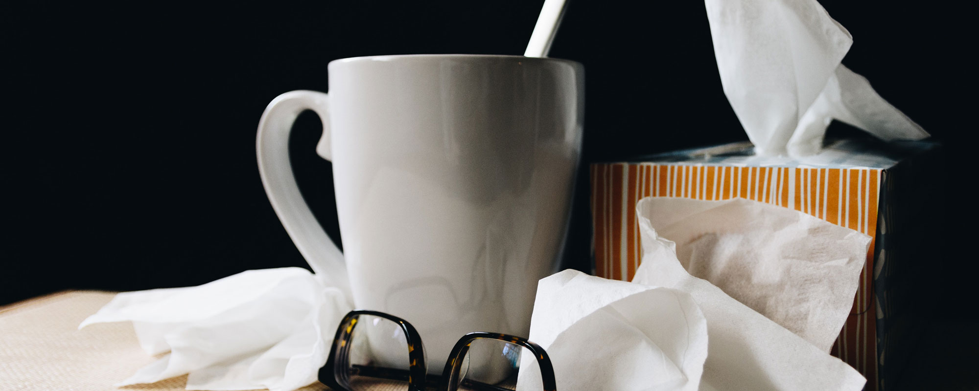 Photo of tissues, a cold remedy and glasses taken off