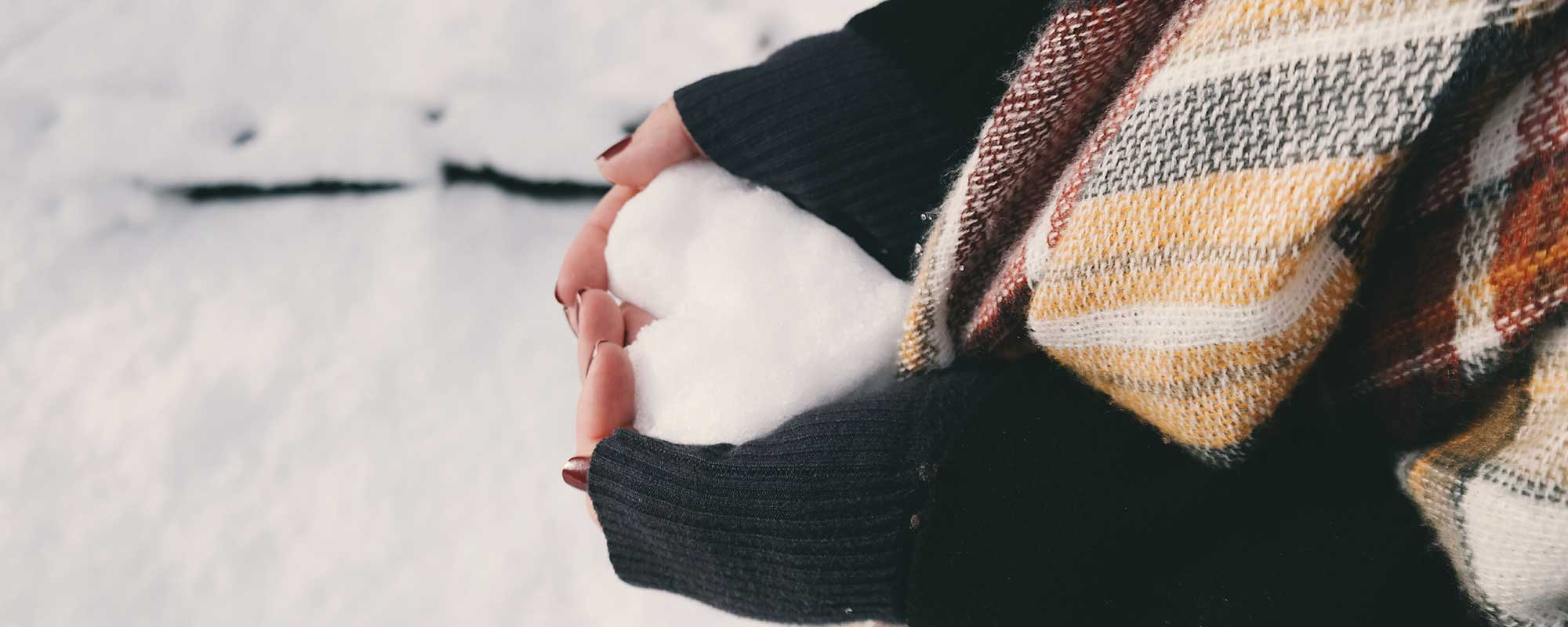 photo of girl in winter making a heart shape with snow