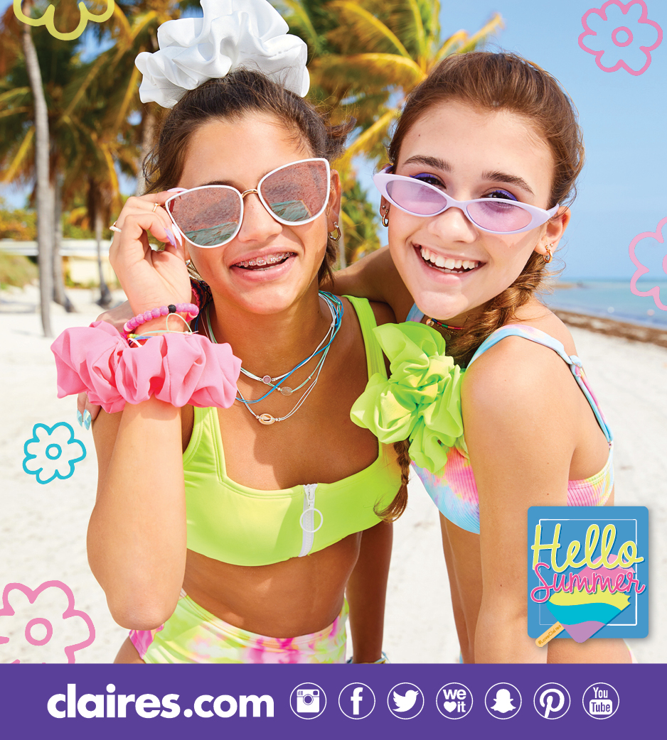 two teenage girls on a beach wearing sunglasses and giant scrunchies that look like big bows in their hair.