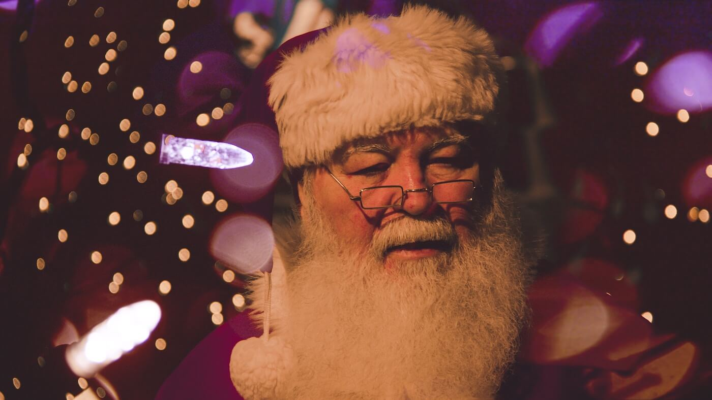 Photo of Santa surrounded by Christmas lights.