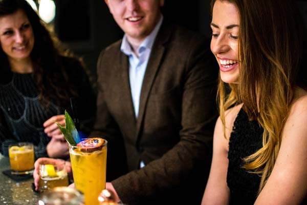 Image of guest smiling after mixologist hands her a drink
