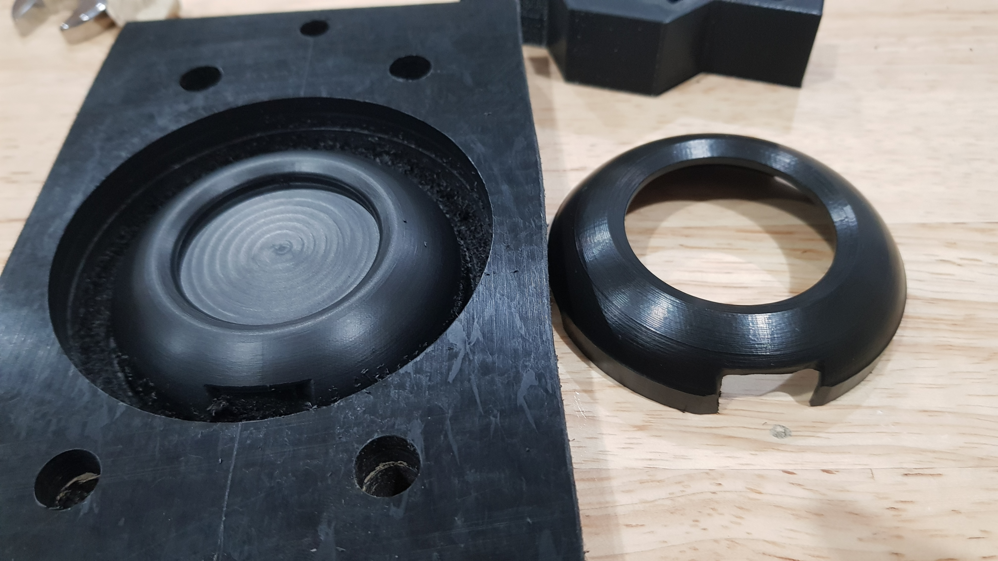 There are two Top parts on the bench. One on the left has a smooth surface with the improvement in toolpathing, one on the right has a rough surface
