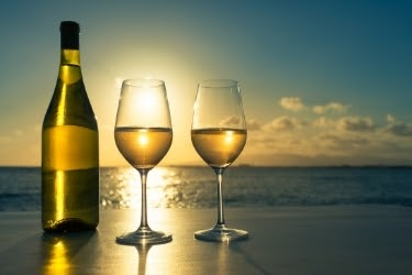 Two glasses of white wine with the bottle, with a view of the beach