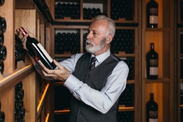 Old man holding a bottle of wine inside a cellar