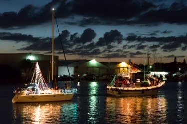 Boats decorated with Christmas lights having a parade