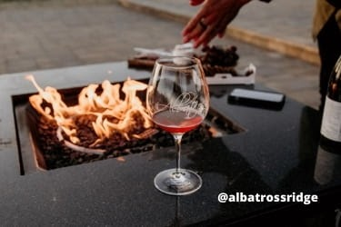 Glass of wine next to a bonfire