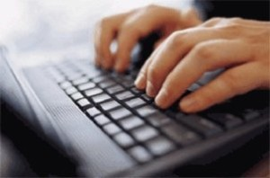 typing twitter message on laptop