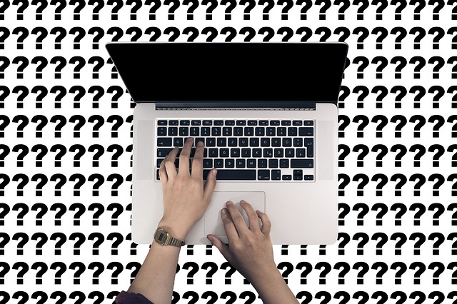 person typing on a computer with question mark background