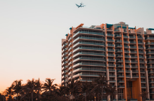 airplane flying over highrise bulding