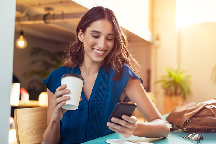 woman smiling at email blast on her phone