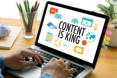 "Man using a laptop showing a graphic that says ""Content is King""."
