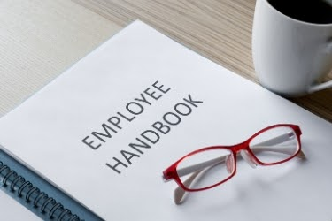Employee Handbook with a pair of glasses on top