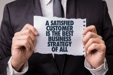 Man holding a paper that says: A satisfied customer is the best business strategy of all.