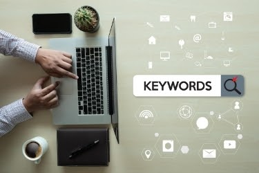 Laptop with a man typing Keywords