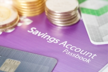 Savings Account Passbook with coins and credit cards