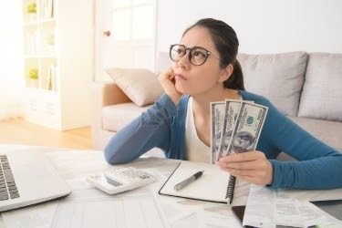 Woman with money in hand thinking of her financial goals