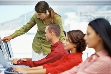 Woman training her staff to use the computer