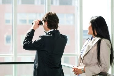Man looking through the window with binoculars