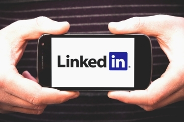 Hands holding a mobile phone with LinkedIn's logo