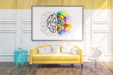 Colorful room with yellow sofa, teal table, white chair and a creative painting