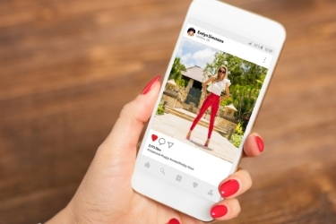 Hands holding a mobile with an Instagram post open