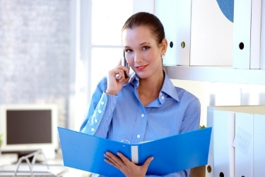 Woman talking through the phone with an open folder